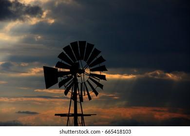 Windmill silhouette, sunset sky.