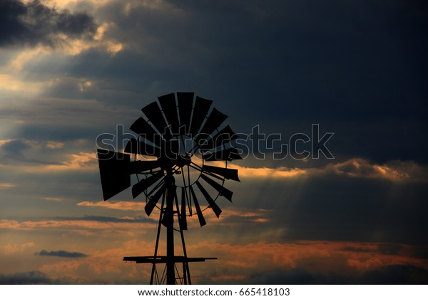 Windmill silhouette, sunset sky.