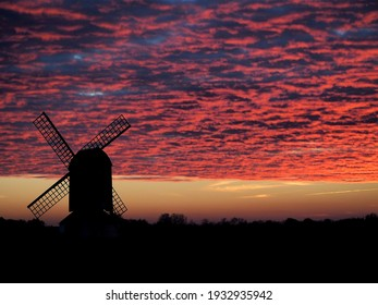 A windmill sits in a field alone, no longer in use it just spends It's days watching the sunrise and sunset.