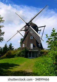 A windmill sits peacefully in the pastoral Danish countryside.