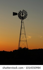 A windmill sits in solitude in a farmer's field.