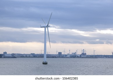 windmill stands in middle of sea against backdrop of industrial area