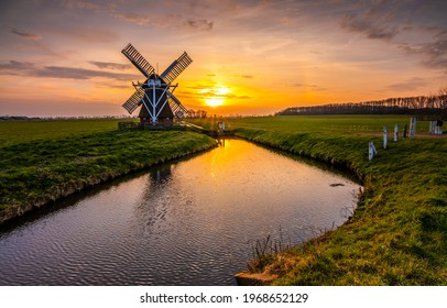 Windmill at sunset river landscape. River mill at sunset. River mill sunset landscape