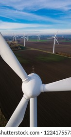 Windmill. Wind farm power station in Europe produce renewable sustainable energy. Wind Turbines aerial view taken with a drone. Wind power technology. Against the sea