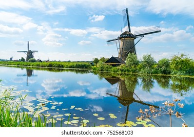 Windmills across and reflected in water in Kinderdijk district popular tourist destination with it's scenic fields, dykes, ponds, canals and windmills near Rotterdam, Holland.