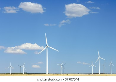 windmills against blue sky with clouds