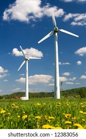 Windmills against blue sky with white clouds and yellow flowers on the ground