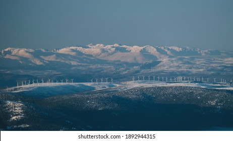 Windmills against snowcapped mountain peaks on a clear blue skies day