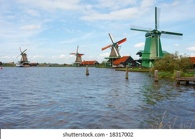 Windmills along the waters-edge at the Zaanse Schans in Holland (near Amsterdam)