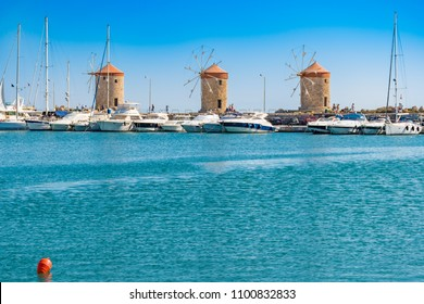 Windmills behind the boats and yachts in Mandraki harbor in City of Rhodes (Rhodes, Greece)