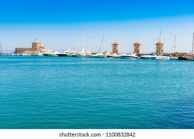 Windmills, boats and St. Nicoaus fortress in Mandraki harbor in City of Rhodes (Rhodes, Greece)