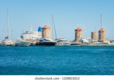 Windmills, boats, yachts and cruise ship in Mandraki harbor in City of Rhodes (Rhodes, Greece)