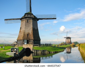 Windmills by a blue canal in the Netherlands in summer
