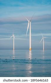 Windmills for electric power production Netherlands Flevoland, Wind turbines farm in sea, windmill farm producing green energy. Netherlands