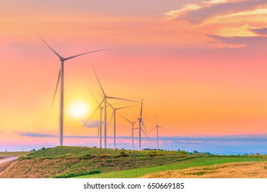 Windmills for electric power production on green field mountain in sunset time sky at Khao Kho, Phetchabun, Thailand