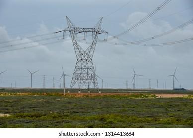 Windmills and electric trellis on a field near Atins on Brazil