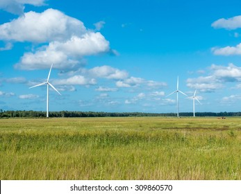 windmills in fields behind blue sky and clouds