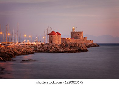Windmills and fortified lighthouse on the harbour pier. Rhodes town, Greece.