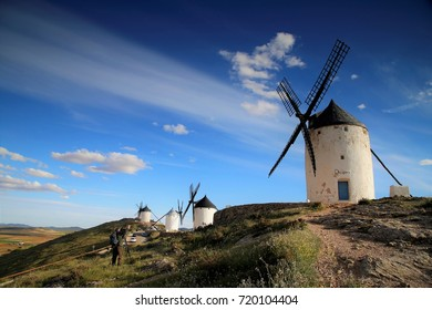 windmills in a line on the hilltop and looking at the farmland beneath, Consuegra, Central Spain, April 9, 2015
