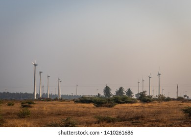 Windmills many heading in one direction parallel view. Wind energy is the real example of developing rural life. Image is taken at dawn. image is taken at Coimbatore