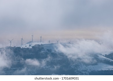 Windmills in the middle of the fog and snow at the top of a mountain