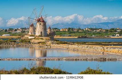 """Windmills at the natural reserve of the """"Saline dello Stagnone"""" near Marsala and Trapani, Sicily."""