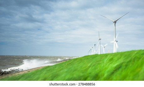Windmills on a Dutch dike in stormy weather along the IJsselmeer in the noordoostpolder in the Netherlands. The axle height is 135 meter and the wings have a peak height of almost 200 meter.