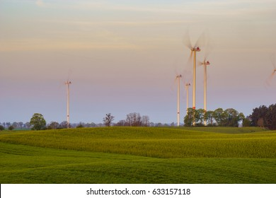 Windmills on the field in the light of the rising sun