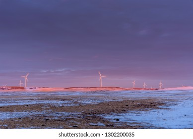 Windmills on a prairie horizon at sunset.  Location is the small town of Dalham close to Drumheller, Alberta Canada.