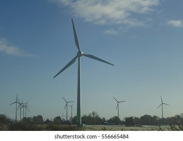 Windmills on the side of the road on blue sky background