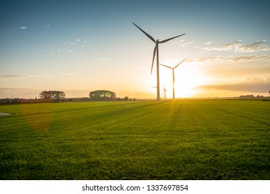 Windmills in open fields in the Netherlands during sunset