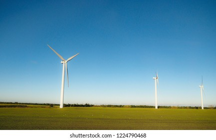 Windmills over flat countryside land in Denmark, green field under clear blue sky