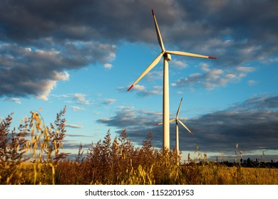 Windmills Power Generators with Sunset Evening Landscape. Wind Mills.