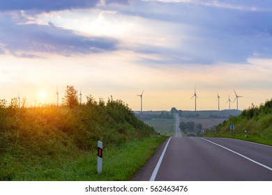 Windmills rotate blades over arable fields and farmland. Electric wind generators produce environmentally electricity. View from height on paved highway early foggy morning. Taurage, Lithuania, Europe