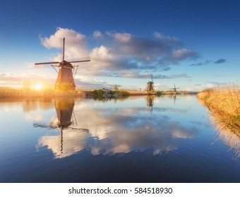 Windmills at sunrise. Rustic landscape with amazing dutch windmills near the water canals with blue sky and clouds reflected in water. Beautiful morning in Kinderdijk, Netherlands in spring. Travel