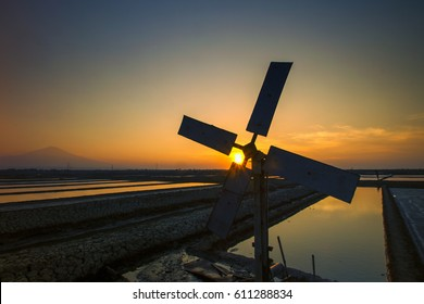 windmills and the sunset in a salt field