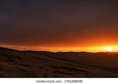 Windmills  at the the top of a mountain in a stunning sunset