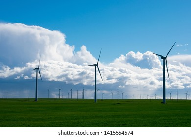 Windmills or wind turbines to generate electricity, on green field with blue sky, sustainable energy
