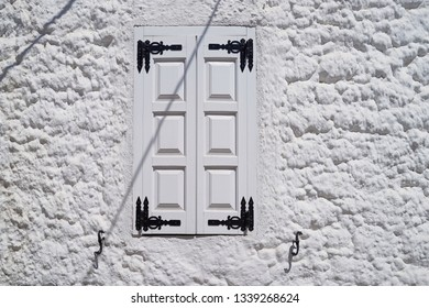 A window against a white wall in the street of the city of Lindos Rhodes island Greece