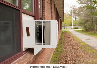 Window air conditioner unit in window in brick building with green grass and leaves on ground on overcast day