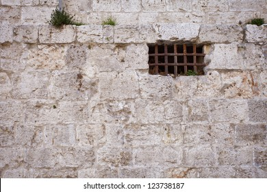Window of an ancient dungeon with stone wall