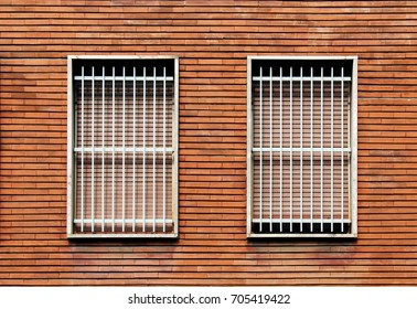 Window bars and closed windows on a bricks wall