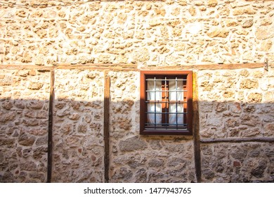 Window with bars in a stone house. The house is built of brown colored stone blocks. The window of the old house is closed with a metal grill.