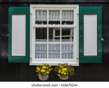 Window in a black wooden house with green and red shutters and two small baskets with flowers in the town of Marken, the Netherlands.