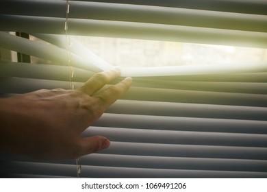 window blinds, sun light coming inside. Conceptual hand