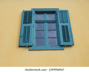 Window with blue or green shutters on a yellow wall