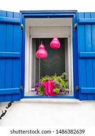 window with blue shutters in greece