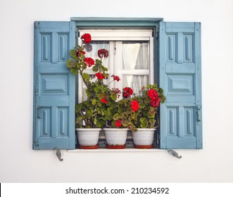 Window with blue shutters and potted geraniums against white background Mediterranean window of a home in the Greek islands.