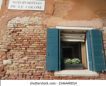 "Window with blue shutters and street sign in Venice, Italy.  ""Sotoportego de le colone"" translates as ""Alleyway under the building of The Colonists."""