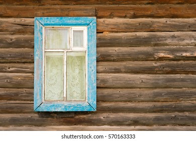 Window with blue wooden frame in an old log house